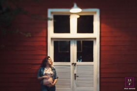 Lifestyle Maternity Portrait Photography in Federal District Brazil | Image contains: woman, barn, red, light, blurry