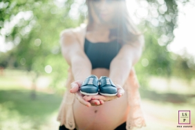 Lifestyle Maternity Portraits in Federal District Brazil - Photo contains: woman, pregnant, trees, outside, baby shoes