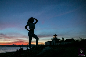 Lifestyle Teen Portrait Photography in Seattle Washington | Image contains: senior, posing, sunset, blue, sky, lighthouse, woman, ocean