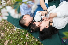 Lifestyle Family Portraits in Hangzhou City Zhejiang - Photo contains: cherry blossoms, outside, kids, mom, blanket, lying down, grass