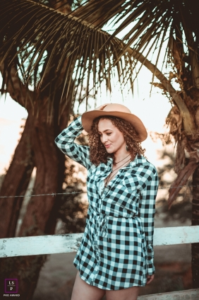 Lifestyle Portraits Session in Minas Gerais Brazil | Photo contains: woman, palm trees, hat, barbed wire, fence