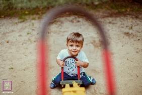 Rio de Janeiro Brazil Family Photography - Lifestyle Portrait contains: outdoor, photo, seesaw, sand, little boy, color, grass, smile