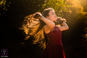 Minas Gerais Brazil Teen Photography - Lifestyle Portrait contains: outdoor, session, solo, teen, girl, hair, sunlight, bushes, red dress, color