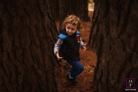 Lifestyle Portrait Photography in Pernambuco Brazil | Image contains: boy, tree trunks, fall, outside, orange, color, photography