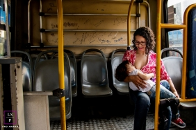 Lifestyle Family Portrait Photography in Santa Catarina Brazil | Image contains: bus, lady, baby, breast-feeding, chairs, color, city, inside