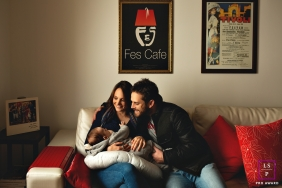 Lifestyle Family Portraits in Rio Grande do Sul Brazil - Photo contains: mother, father, baby, couch, pillows, pictures, wall, color, red