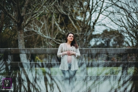 Lifestyle Maternity Portrait Photography in Rio Grande do Sul Brazil | Image contains: trees, fence, mother to be, reflection, color, outdoors