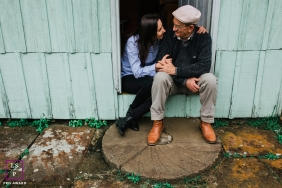 Lifestyle Family Portrait Session in Rio Grande do Sul Brazil | Photo contains: old man, young lady, blue, barn, stone, door, color, sitting down