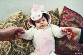 Lifestyle Baby Portrait Photography in Rio Grande do Sul Brazil | Image contains: unicorn, baby, pillows, mother's hand, father's hand, color