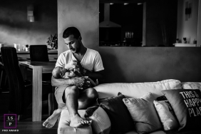 Family Portraits in Bourgogne-Franche-Comte France | Lifestyle Photography Session contains: father, baby, infant, home, sofa, feeding, bottle, black and white