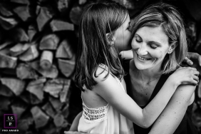 Family Photographer in Bourgogne-Franche-Comte France | Lifestyle Image contains: mother, daugther, wood pile, black and white