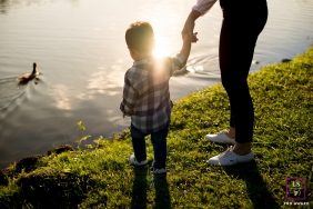 Family Portraits in London England | Lifestyle Photography Session contains: mother, sun, grass, pond, duck