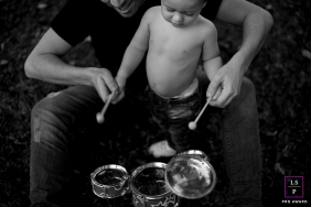 Family Photography for London England - Lifestyle Portrait contains: father, son, toy drums, play, black and white