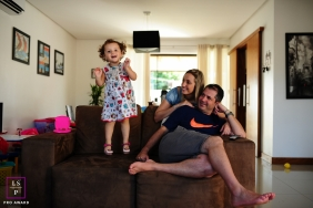 Family Portraits in Rio Grande do Sul Brazil | Lifestyle Photography Session contains: mother, father, home, sofa, girl, jump