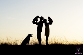 Family Photographer in Key West Florida | Lifestyle Image contains: mother, father, baby, dogs, field, silhouettes