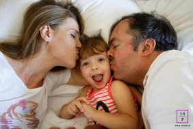 Family Portraits in Rio de Janeiro Brazil | Lifestyle Photography Session contains: father, mother, daughter, kiss, bed
