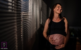 Maternity Photographer in Rio Grande do Sul Brazil | Lifestyle Image contains: woman, pregnant, smile, window, blinds, shadows