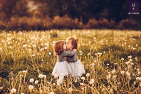 Family Photography for Barcelona Spain - Lifestyle Portrait contains: girls, kiss, portrait, field, dandelions, outdoors