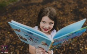 Family Photographer in Sao Paulo Brazil | Lifestyle Image contains: girl, outdoors, book, happy