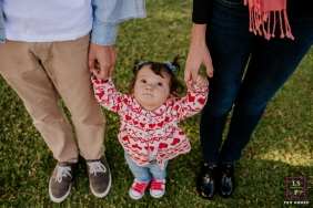 Family Photographer in Florianopolis Santa Catarina | Lifestyle Image contains: toddler, girl, overhead, mother, father, grass