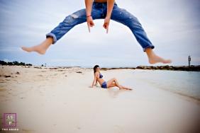 Couple Photographer in Florianopolis Santa Catarina | Lifestyle Image contains: woman, beach, shoreline, jetty, leap, man