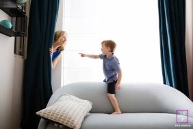Marseille Family Lifestyle Portrait Photography Bouches-du-Rhone | Image contains: mom, boy, pointing, play, hide-and-seek, living room, couch, sofa, pillow, window, curtain, peek-a-boo
