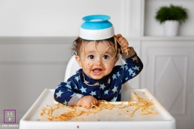 Marseille Baby Lifestyle Portrait Photography Bouches-du-Rhone | Image contains: toddler, kitchen, food, highchair, spaghetti, mess, bowl, on head