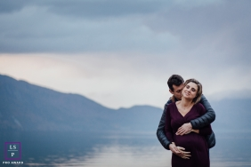 Auvergne-Rhone-Alpes Maternity Lifestyle Portrait Session France | Photo contains: couple, water, lake, hills, hug, love