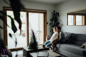 Auvergne-Rhone-Alpes Maternity Lifestyle Portraits France - Photo contains: couple, home, pregnancy, couch, sofa, living room, window, yard