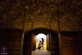 Rio Grande do Sul Lifestyle Maternity Portrait Session Brazil | Photo contains: couple, pregnancy, kiss, belly, stable, stone, wood, doorway, framed, art