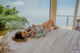 Rio de Janeiro Maternity Lifestyle Portrait Photography Brazil | Image contains: woman, bedroom, bed, overlook, ocean, water, shore, windows