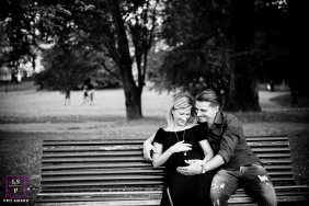 Pistoia Tuscany Couple Lifestyle Portrait with Baby Bump at the Park - Photo contains: black and white, husband, wife, bench, trees, grass