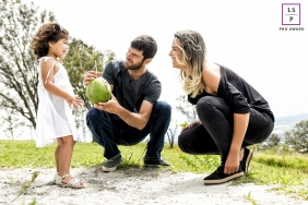 Sete Lagoas Minas Gerais Family Lifestyle Portrait Session with Mom, Dad and Daughter | Photo contains: husband, wife, child, coconut, straw, park