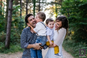 France Family Hugs Lifestyle Photography | Image contains: father, mother, sons, road, trees, color, kisses, photo shoot