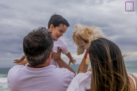Macae Family Lifestyle Photography at the Beach | Image contains: ocean, sky, father, mother, son, dog, color, photo