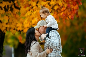 Seattle Family Lifestyle Portraits - Photo contains: family, three, fall, leaves, outdoors, girl, kiss