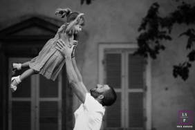Lyon Lifestyle Portrait Photography for Auvergne-Rhone-Alpes | Image contains:  father, daughter, toss, building, windows, outdoors
