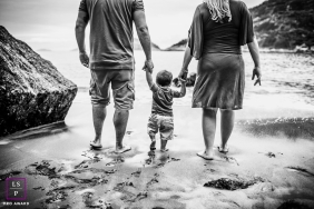 Sao Paulo Lifestyle Family Portraits at the Beach | Image contains: beach, rock, sand, footprints, boy, color, family, black, white
