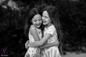 Florianopolis Lifestyle Sister Photography | Portrait contains: girls, outdoors, black, white, hug, laughing, dresses, trees