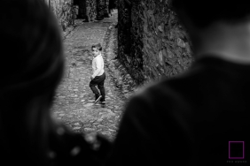 Haute-Garonne lifestyle photographer for Occitanie - Parents and boy walking in old street in black and white photography