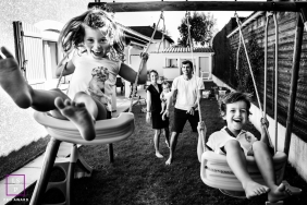 Backyard Family Photography for Auvergne-Rhone-Alpes - Lifestyle Portrait: Black and White family moment around the swing