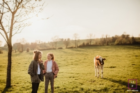 Family Photography for Liège Wallonie - Lifestyle Portrait: The girl cousins in the countryside with a calf