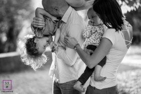 Family Photographer in Auvergne-Rhone-Alpes | Lifestyle Image contains: mom, dad, toddler, baby, hug, yard, grass, black and white, play