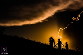 Family Photographer in Minas Gerais | Lifestyle Image from Brazil contains:  mom, dad, children, silhouette, clouds, hill, field