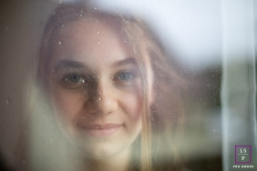 Amandine Fenix lifestyle portrait of a young woman. Blurry reflections in the glass window.