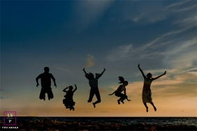 France photo session on the beach of a family jumping in this silhouette shot by the water.