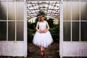 Parana maternity session in the doorway of a greenhouse and the woman wearing red pointe ballet shoes.