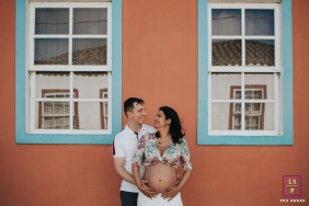Santa Catarina Lifestyle Maternity Portrait session of a couple standing next to a building between two windows.