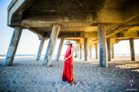 An expecting mother poses for a San Francisco maternity portrait session under a pier at the ocean.