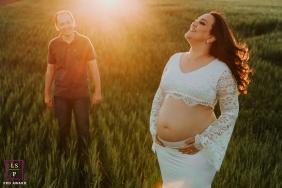 Brazilian couple poses in a field during a lifestyle maternity photoshoot